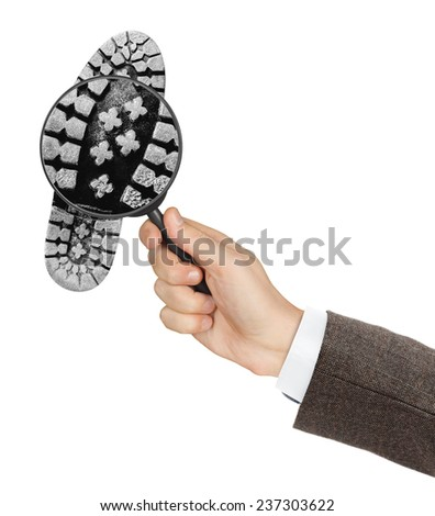 Magnifying glass in hand and shoe printout isolated on white background - stock photo