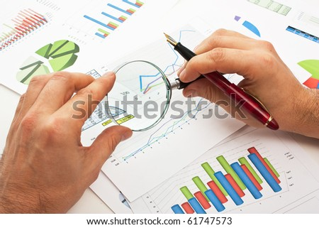 magnifying glass in hand and working paper chart - stock photo