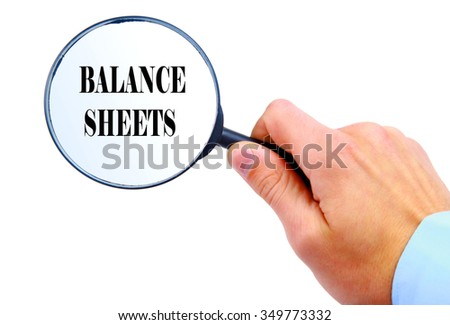 "Magnifying glass in hand isolated on white background searching ""Balance Sheets"""