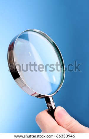 Magnifying glass in woman hand on blue background - stock photo