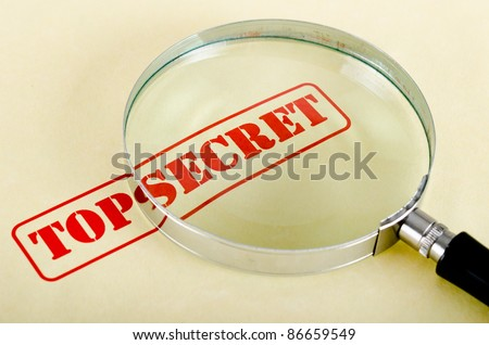 magnifying glass is on top secret inscription - stock photo