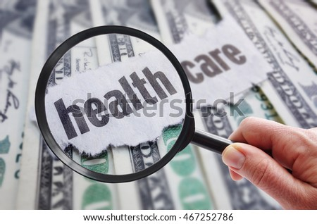 Magnifying glass looking at health care newspaper headline, on cash