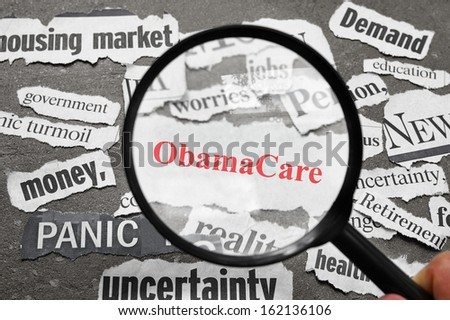 Magnifying glass looking at newspaper headlines, with ObamaCare in red - stock photo