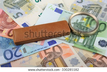 Magnifying glass lying on Euro banknotes, closeup, shallow DOF - stock photo