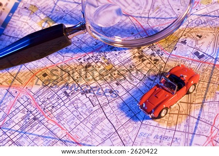 Magnifying glass, map and toy car - stock photo