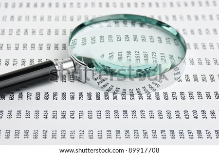 magnifying glass on a document with columns of figures - stock photo