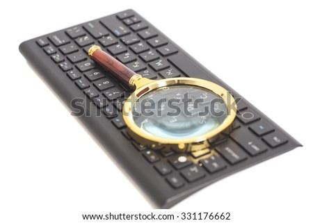 Magnifying Glass on black keyboard isolated - stock photo
