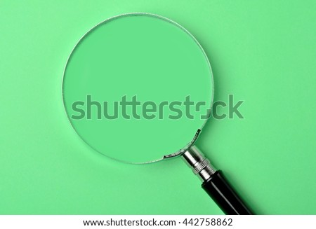 Magnifying glass on green background closeup - stock photo