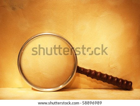 magnifying glass on old yellow paper - stock photo