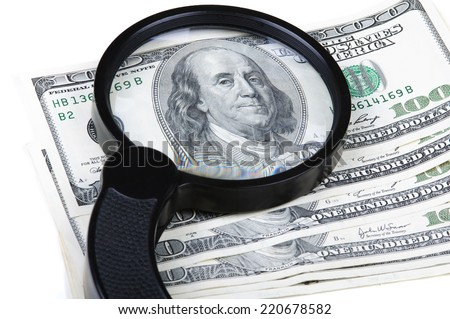 Magnifying glass on the notes of a hundred dollars. Isolated on white background. - stock photo