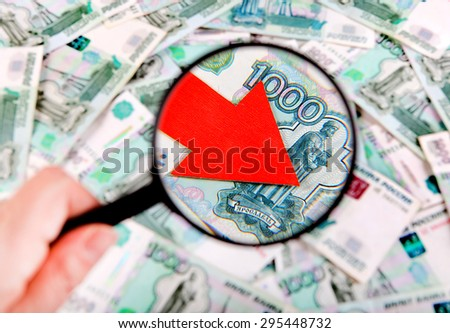 Magnifying Glass on the Russian Currency Background with Arrow Down - stock photo