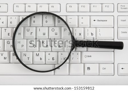 Magnifying glass on white keyboard close up  - stock photo