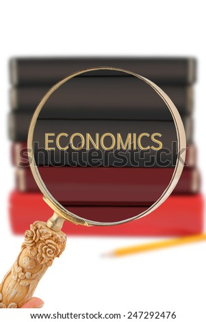 Magnifying glass or loop looking on an educational university subject - Economics - stock photo