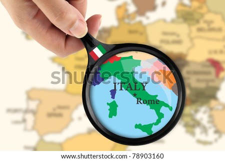 Magnifying glass over a map of Italy - stock photo