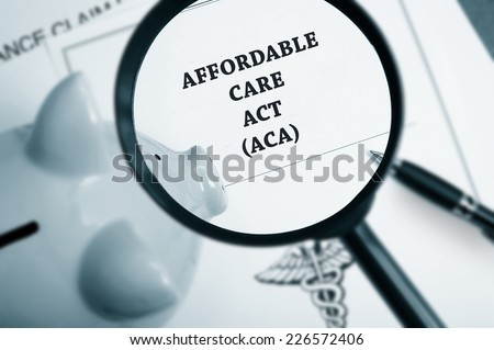 Magnifying glass over Affordable Care Act policy and piggy bank - stock photo