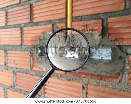 magnifying glass over electric sockets installation in brick walls at house construction site - stock photo