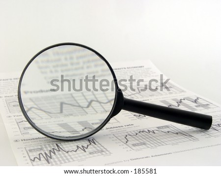 magnifying glass over financial newspaper - stock photo