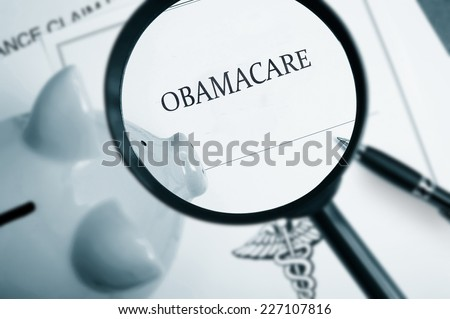Magnifying glass over Obamacare policy and piggy bank - stock photo