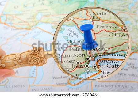 magnifying glass over Toronto, Canada map with destination tack