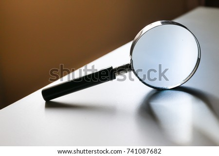 magnifying glass put on white table with sunlight and reflection of light