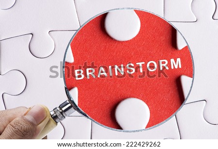 """Magnifying glass searching missing puzzle peace """"BRAINSTORM"""" - stock photo"""