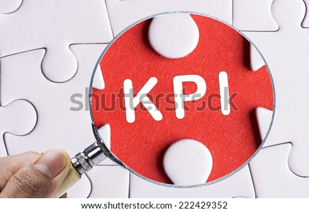 "Magnifying glass searching missing puzzle peace ""KPI"" - stock photo"