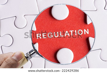 """Magnifying glass searching missing puzzle peace """"REGULATION"""" - stock photo"""
