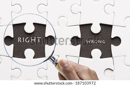 "Magnifying glass searching missing puzzle peace ""RIGHT""  - stock photo"
