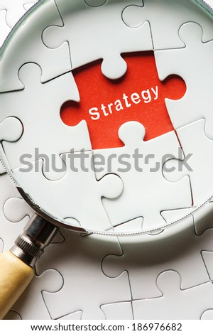 "Magnifying glass searching missing puzzle peace ""STRATEGY"" - stock photo"