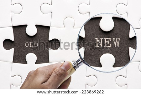 """Magnifying glass searching missing puzzle peaces """"Old and New""""  - stock photo"""
