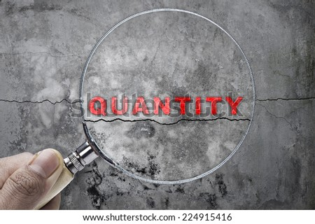 """Magnifying glass searching """"Quantity"""" over cracked wall as a background - stock photo"""