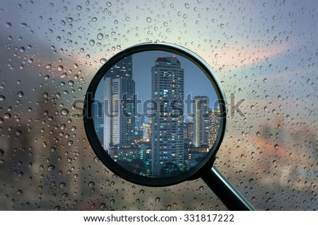 magnifying glass with Bangkok cityscape on Waterdrops over a glass surface windows with cityscape background, business concept - stock photo