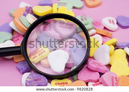 Magnifying glass with candy hearts on pink background