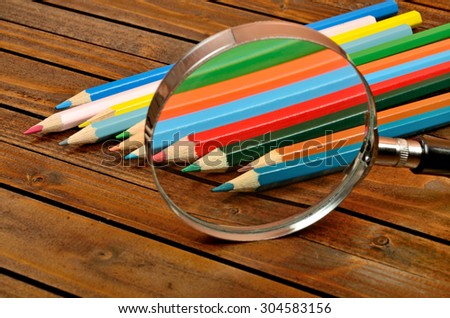 Magnifying glass with colorful pencil on wooden table