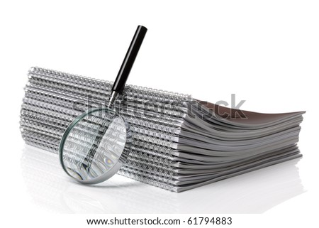 Magnifying glass with stack of spiral notebook documents - concept for searching for a file - stock photo