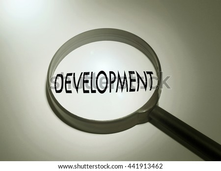 Magnifying glass with the word development. Searching development - stock photo