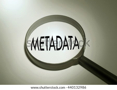 Magnifying glass with the word metadata. Searching metadata - stock photo