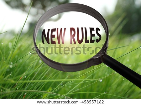 Magnifying glass with the word new rules on grass background. Selective focus - stock photo