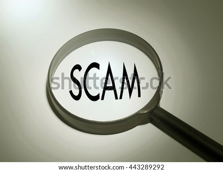 Magnifying glass with the word scam. Searching scam - stock photo