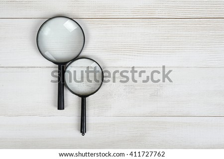 Magnifying glasses lying on a wooden surface with open space in top view - stock photo