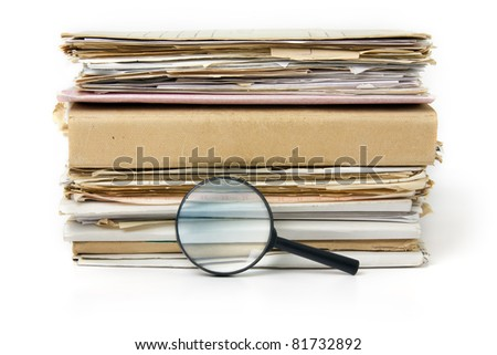 Magnifying lens  on the background of the stack of old paper files - stock photo