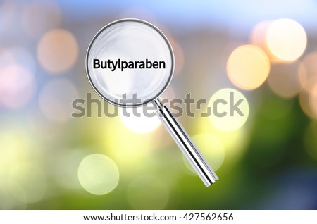 Magnifying lens over background with text Butylparaben, with the blurred lights visible in the background. 3D rendering. - stock photo