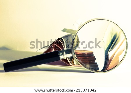 magnifying money photo with money and magnifying glass - stock photo