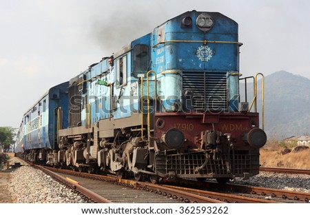 MAHARASHTRA, INDIA - CIRCA MARCH 2014: Indian train pulled by a diesel locomotive on the Konkan Railway nears Magalore in western India - stock photo