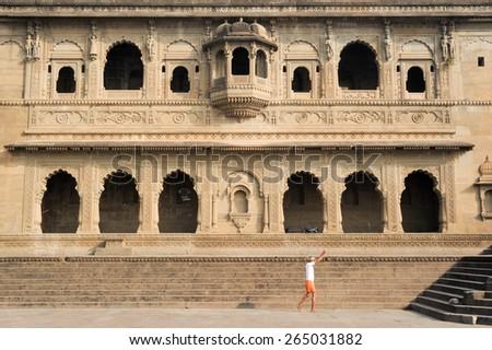 Maheshwar, India - 3 February 2015: People walking in front of Maheshwar palace on India - stock photo