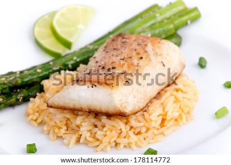 mahi mahi fish fillet on rice with asparagus - stock photo