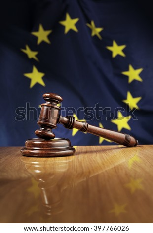 Mahogany wooden gavel on glossy wooden table. Flag of European Union, EU,  in the background.