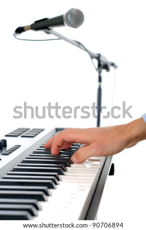 maicrophone and male hands playing the piano in the studio isolated on white - shallow pepth of firld with focus plased on hand - stock photo