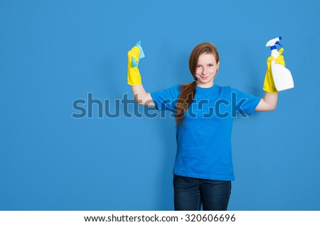 Maid cleaning woman with cleaning spray bottle. Cleaning service. Portrait of beautiful cleaning girl isolated on blue background with copyspace. Mixed race woman. - stock photo