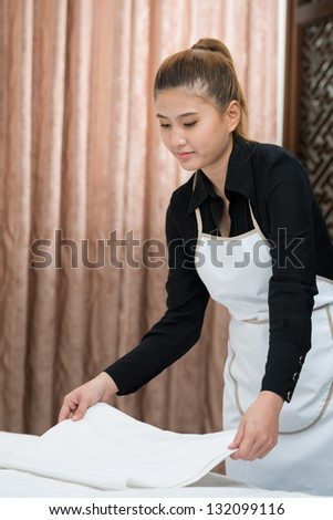 Maid holding towels in a hotel - stock photo